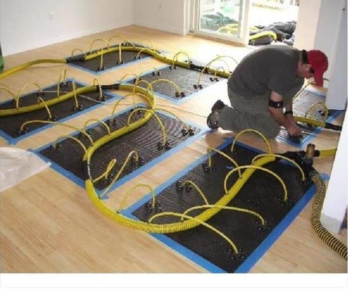 Worker installing black mats with the drying hoses protruding from the mats