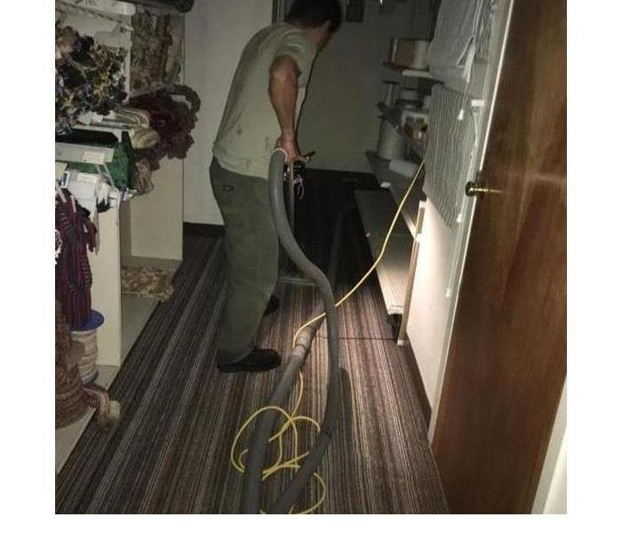 worker with a carpet wand and hoses extracting water from the carpet