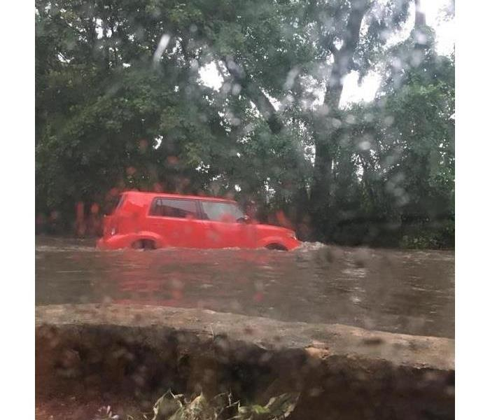 Red car driving through large amount of water