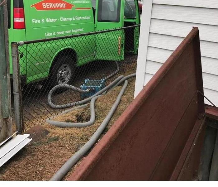 Green SERVPRO truck with hoses coming out the back door